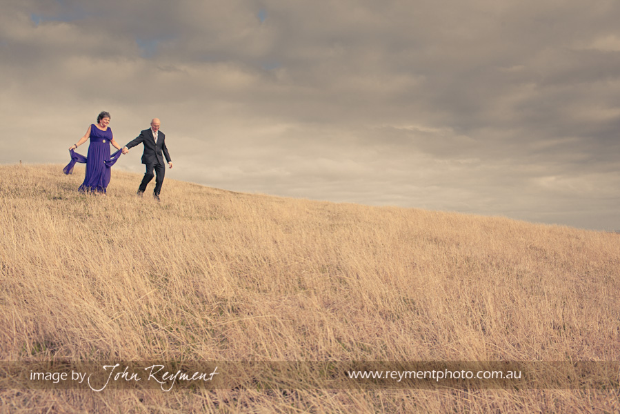 bride and groom on grassy slopes, Camperdown, Victoria, wedding photography, John Reyment